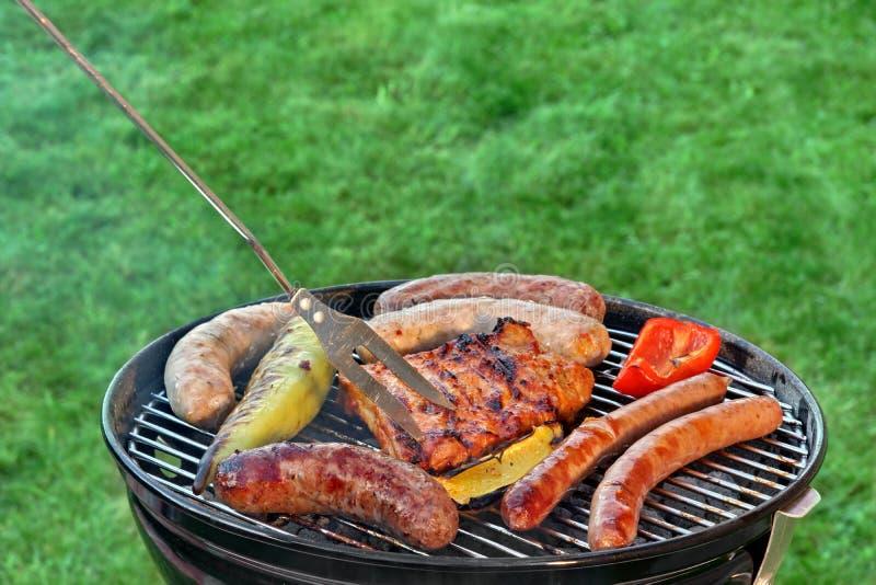Heißer BBQ-Grill mit sortiertem Fleisch auf dem Garten-Rasen stockbilder