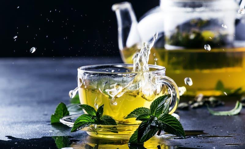 Heißer chinesischer grüner Tee mit Minze, wenn das Spritzen aus dem KE gießt stockfoto