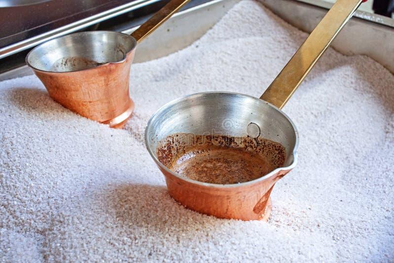 Heißer geschmackvoller Kaffee vom kupfernen cezve vorbereitet auf heißen Sand Cezve zur Küche lizenzfreie stockfotos