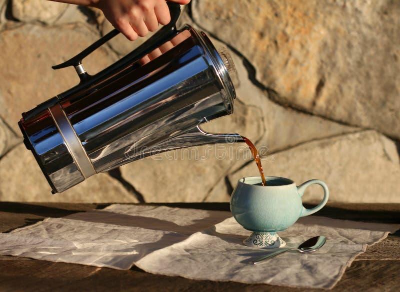 Heißer Kaffee, der in Schale ausgelaufen wird stockfotografie