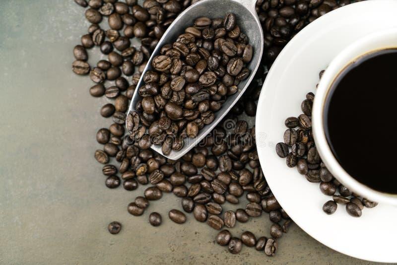 Heißer Kaffee in der weißen Schale mit BratenKaffeebohnen und Schaufel auf Steintabellenhintergrund lizenzfreies stockfoto