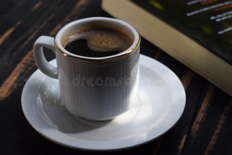 Heißer Kaffee des Morgens auf dem Tisch nahe dem Buch lizenzfreies stockbild