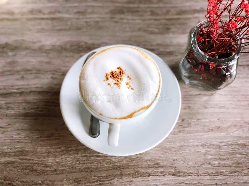 Heißer Kaffee in einer weißen Schale auf Marmortabelle und Blumenvase lizenzfreie stockfotos