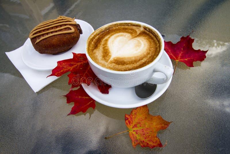 Heißer Kaffee Latte mit Nachtisch auf kühlen Autumn Day stockfotos