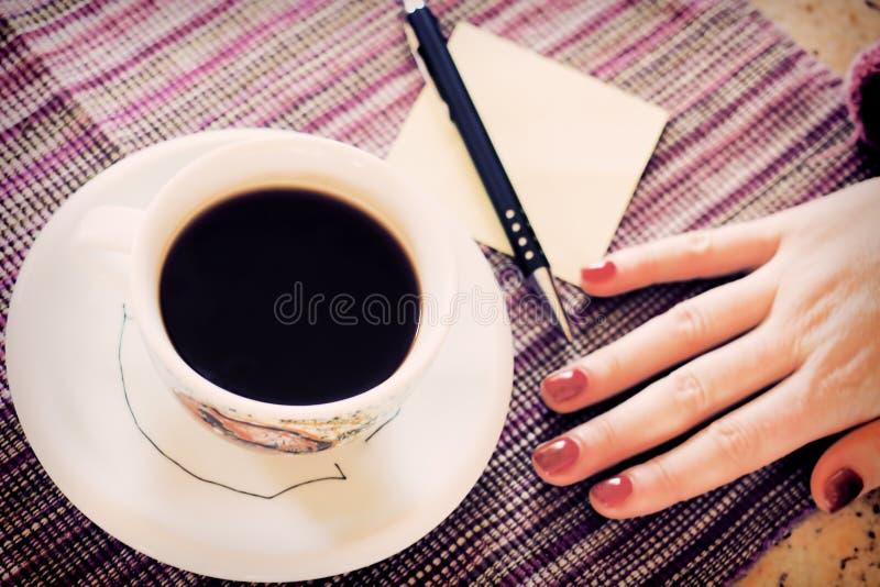 Heißer Kaffee mit Anmerkung des leeren Papiers lizenzfreie stockfotografie