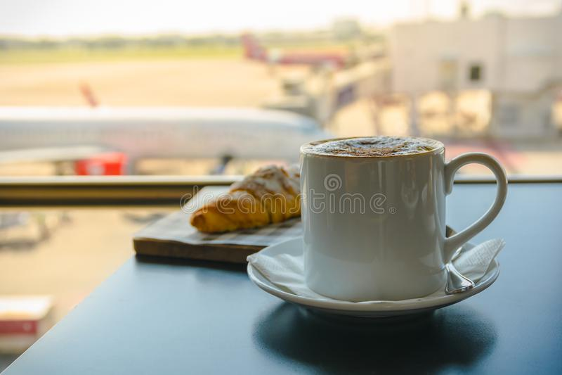 Heißer Kaffee mit Frühstück am Flughafenaufenthaltsraum stockfotos