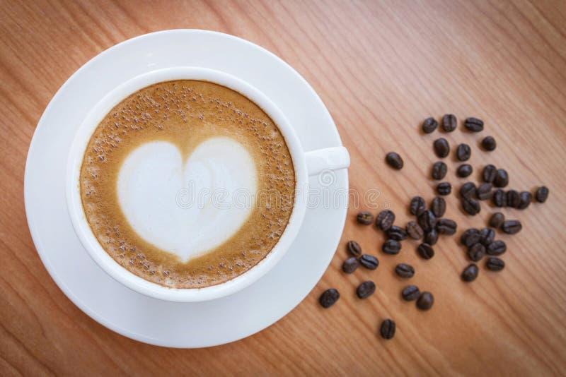 Heißer Kaffee mit Herzmuster in der weißen Schale stockbild