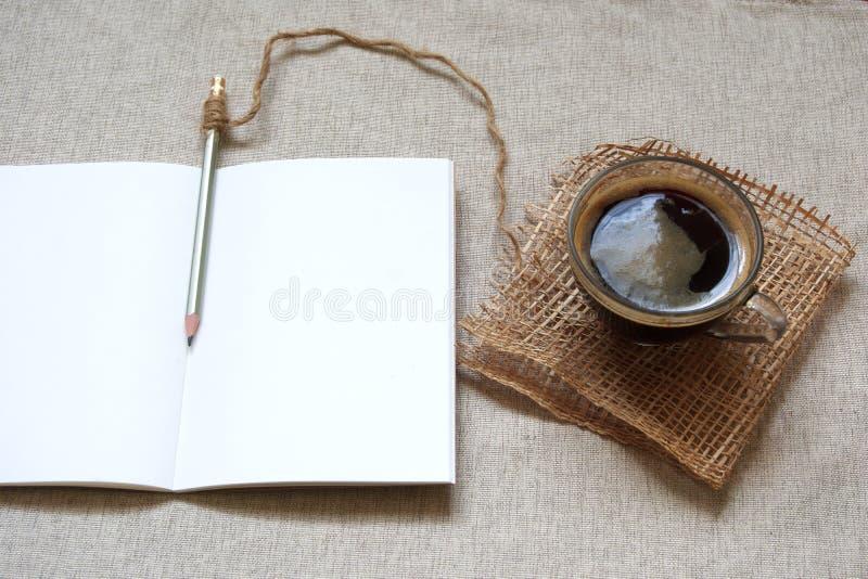 Heißer Kaffee und leeres Notizbuch für einen Morgen Programm zapfend lizenzfreie stockbilder