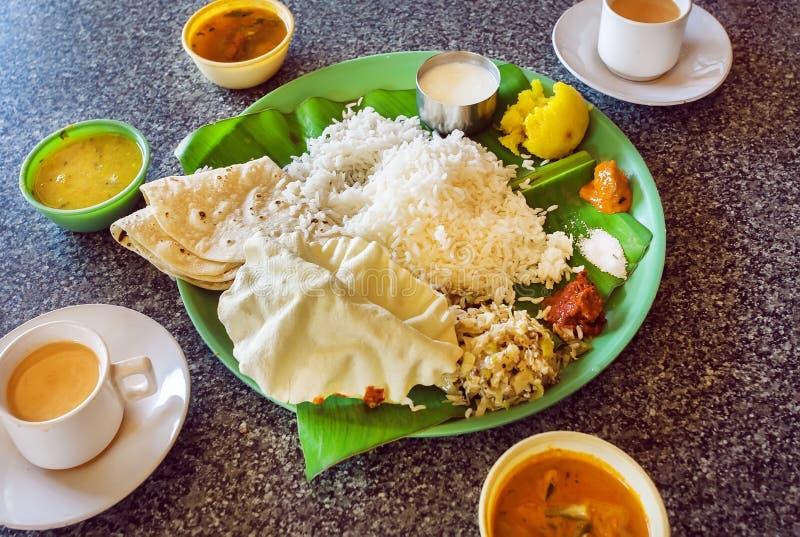 Heißer Kaffee und Platte mit indischem Lebensmittel Südthali mit Reis und würzigem Gemüse, auf Palmblatt im indischen Café lizenzfreies stockfoto