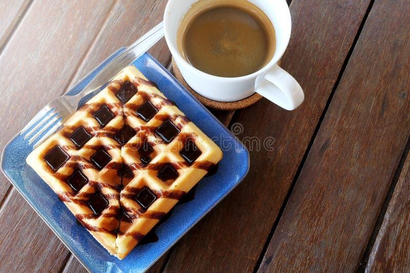 Heißer Kaffee und Waffeln mit Schokoladensoße auf Holztischhintergrund lizenzfreie stockbilder