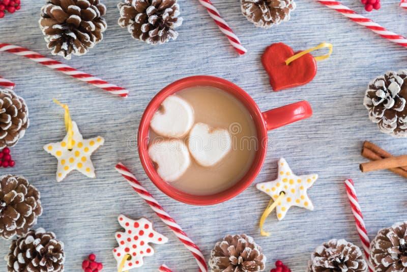 Heißer Kakao im roten Becher mit Herzeibischen legen flach Anordnung Weihnachten lizenzfreie stockfotos
