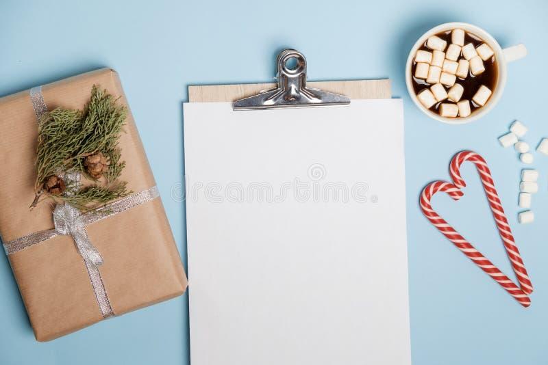 Heißer Kakao mit Eibischen und Laptop, Süßigkeiten auf einer blauen Tabelle stockfotografie