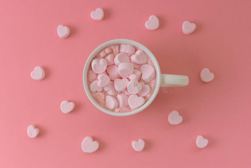 Heißer Kakao mit rosa Herzen formte Eibische auf rosa Hintergrund lizenzfreie stockfotografie