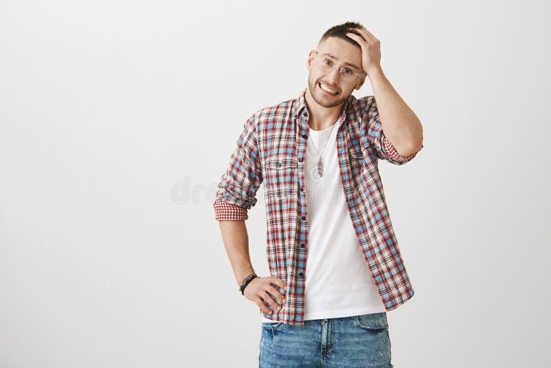 Heißer kreativer junger Mann mit stilvollen Gläsern und Haarschnitt, besorgt lächelnd beim Berühren des Haares und halten Hand au stockfotografie