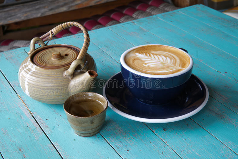 Heißer Kunst Lattekaffee und -tee in einer Schale auf blauem Holztisch lizenzfreie stockbilder