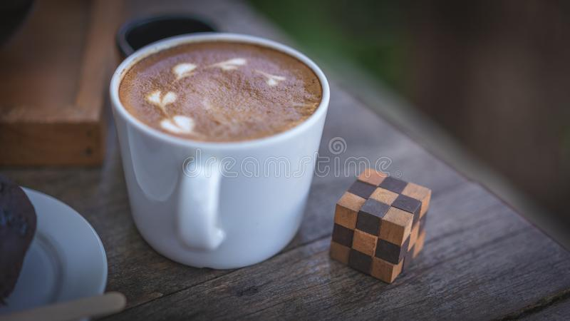 Heißer Latte-Kaffee und hölzerne Kubikpuzzlespiel-Fotos stockbild