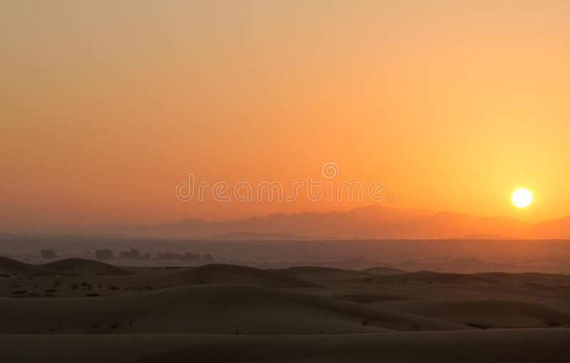 Heißer Sonnenaufgang in den Wüstendünen von Dubai, Vereinigte Arabische Emirate stockfotografie