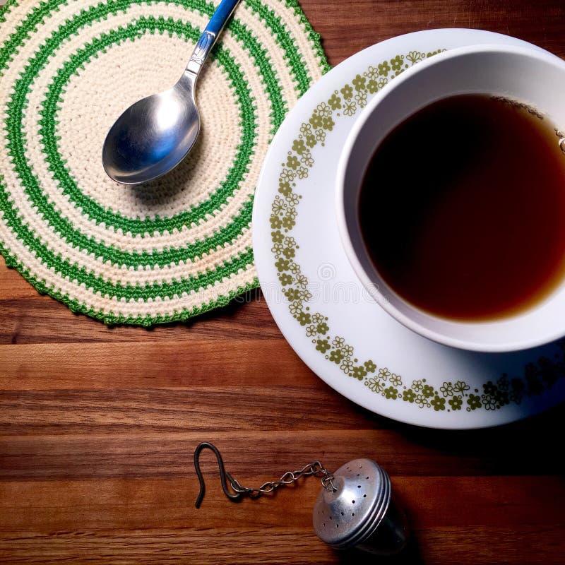 Heißer Tee auf Metzgerblocktafel mit Weinlesedoily und -löffel stockbild