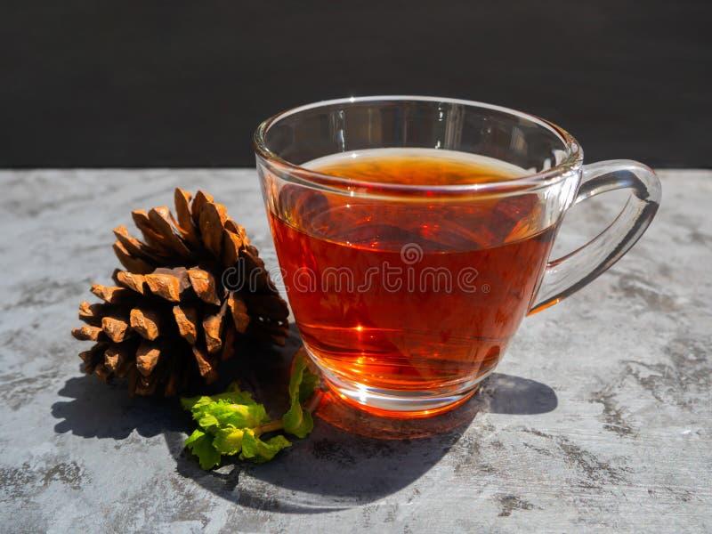 Heißer Tee in einem Klarglas, das auf ein dunkelgraues gesetzt wird lizenzfreies stockfoto