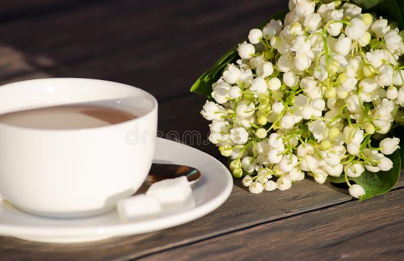 Heißer Tee in einer weißen Schale mit einem Blumenstrauß von Blumen stockfotografie