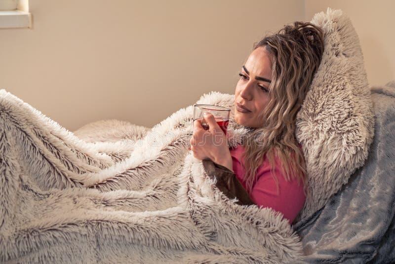 Heißer Tee mit Zitrone in der kranken Frau des Betts, trinkender Kräutertee Vitam lizenzfreie stockfotografie