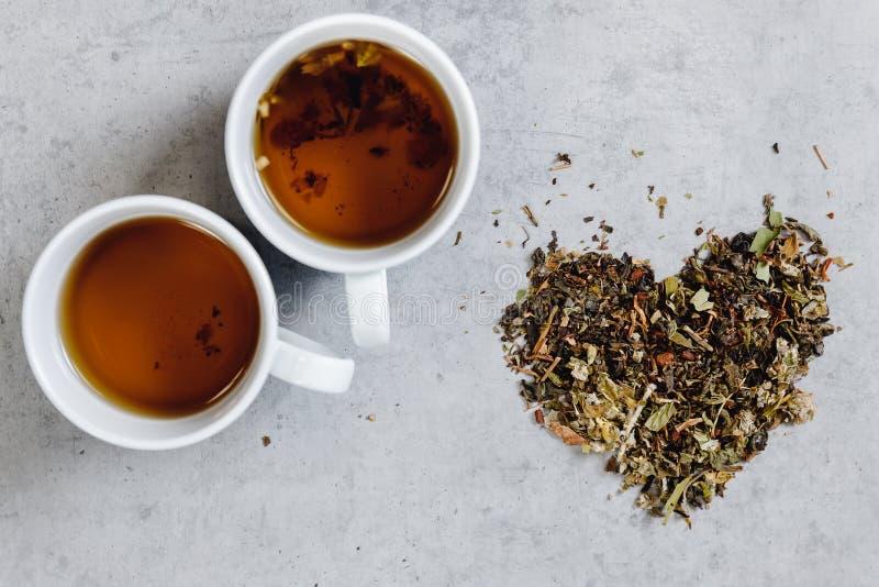 Heißer Tee zwei Glasbecherstände auf grauem Hintergrund, Herz formte Blätter Konzeptdatum, Romanze stockfotos