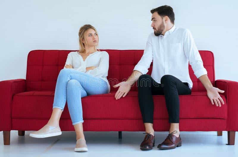 Heißes ausgeglichenes Streiten des Ehemanns mit Fraukonflikt und Bohren von zwei Paaren im Wohnzimmer, negative Gefühle lizenzfreie stockfotografie