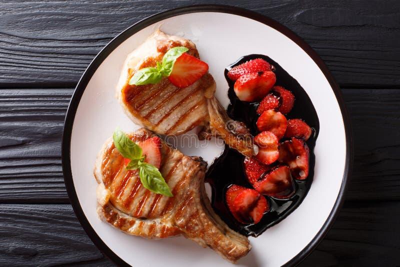 Heißes gegrilltes geschmackvolles Schweinekotelett mit balsamischer Erdbeernahaufnahme an lizenzfreie stockfotos