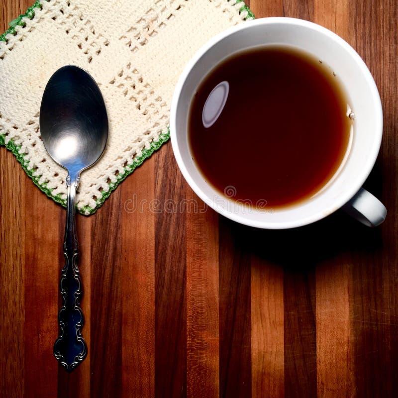 Heißes Getränk auf Metzgerblocktafel mit Weinlesedoily und -löffel stockfotos
