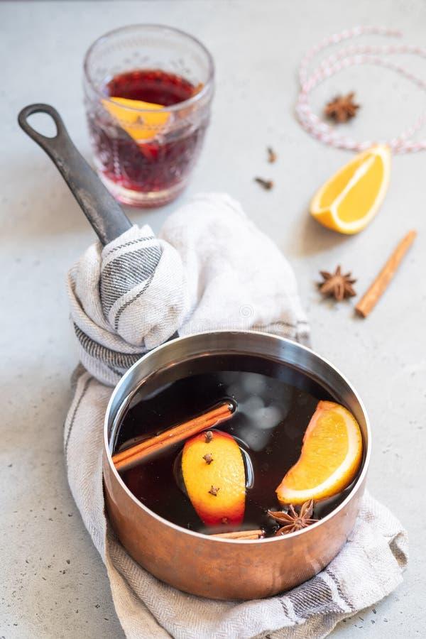 Heißes Getränk des Glühweins mit Orangen und Gewürzen im kupfernen Topf stockbild