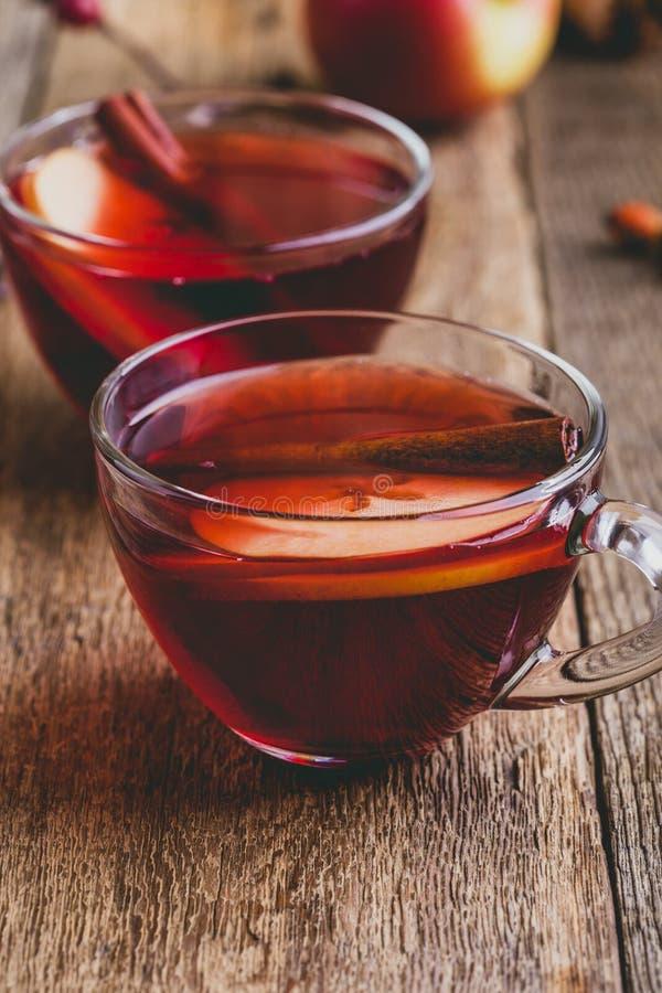 Heißes Getränk mit Apfelwein, geschnittener Frucht und Zimtstange stockbilder