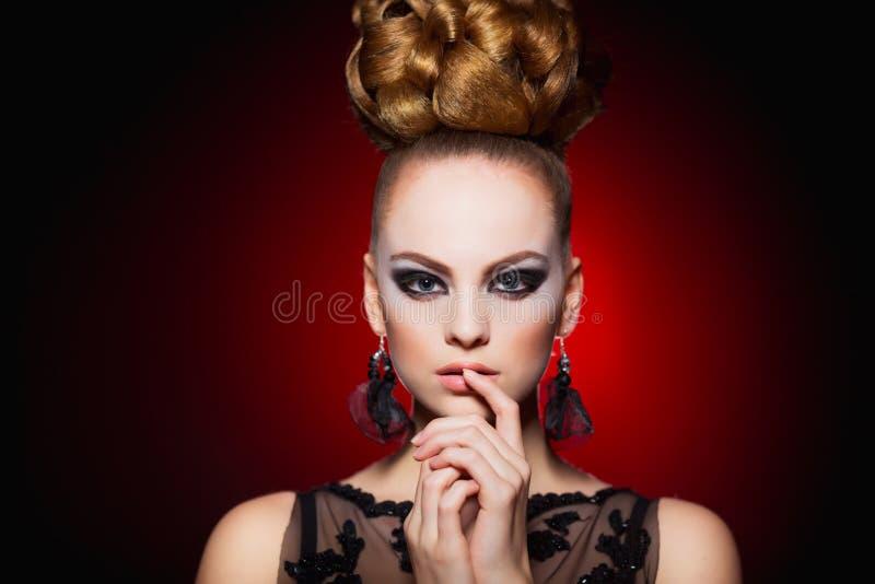 Heißes Modell der jungen Frau mit sexy Lippenmake-up, starken Augenbrauen, sauberer glänzender Haut und Brötchenfrisur Schöne Art lizenzfreie stockfotografie