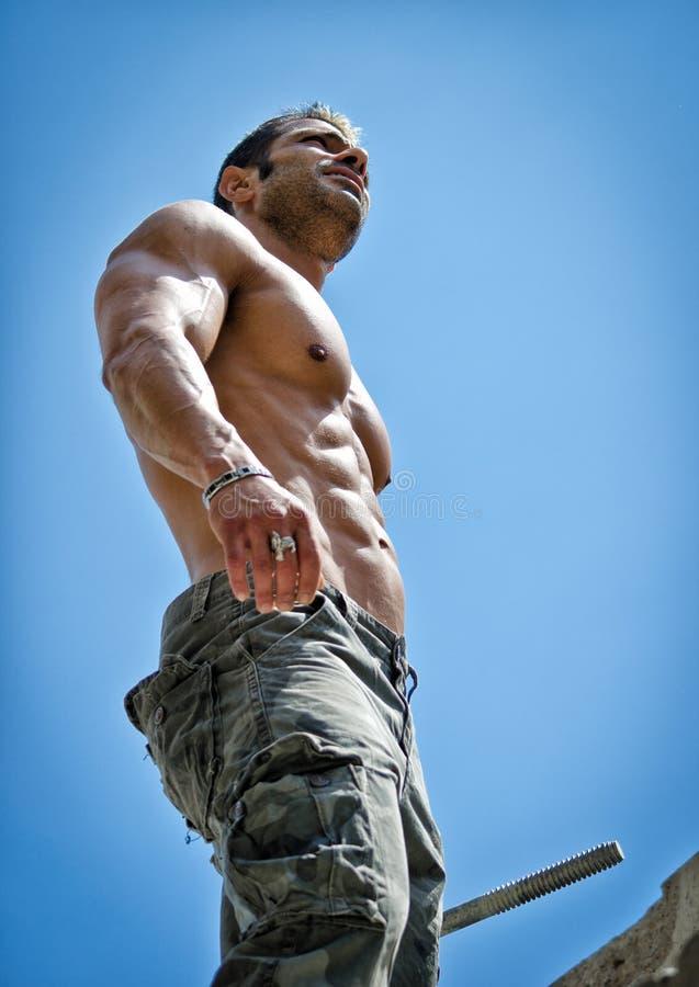 Heißes, muskulöses Bauarbeiterhemdloses von unterhalb gesehen lizenzfreies stockfoto