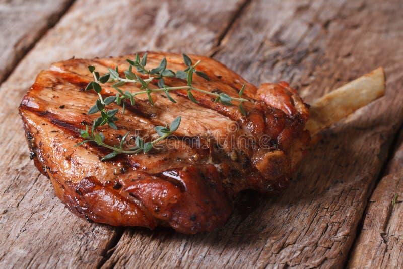 Heißes saftiges Schweinefleischsteak mit Thymian auf einer alten Tabelle lizenzfreies stockbild