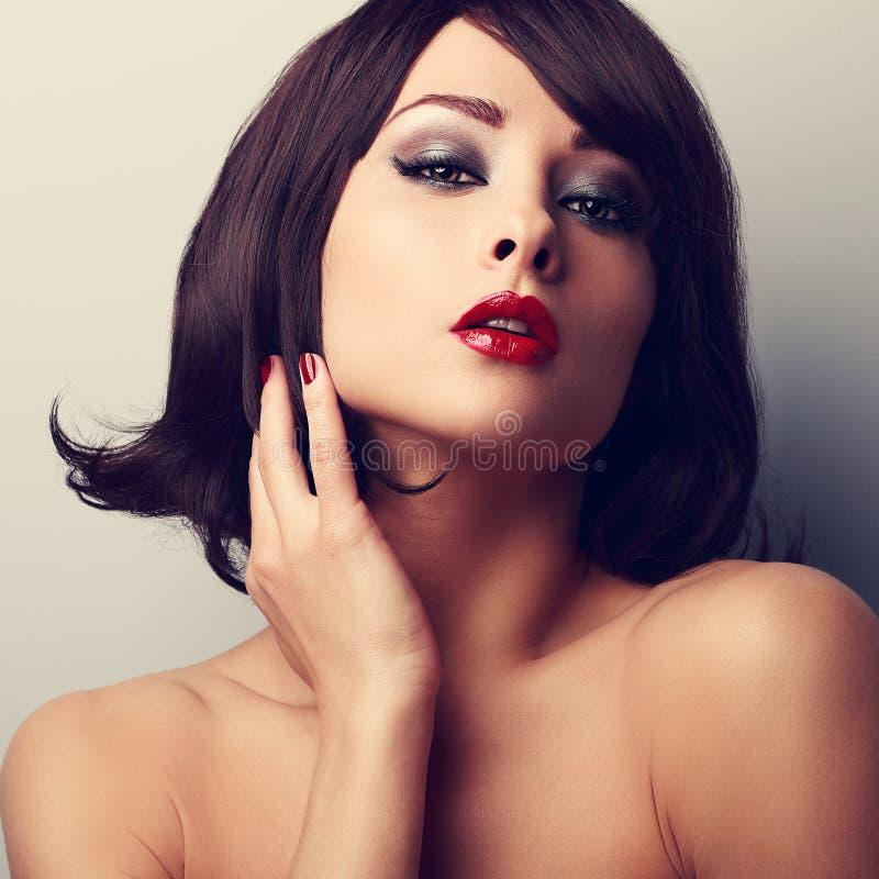 Heißes sexy Make-upmodell mit kurzer schwarzer Frisur und rotem lipsti stockfoto