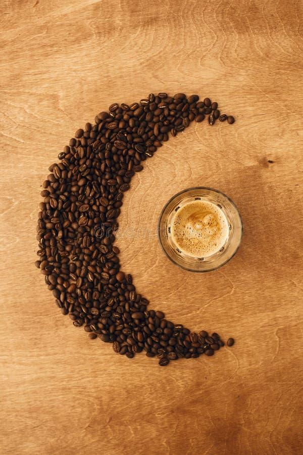 HeißEspresso mit Schaumschaum in Glasbecher und aromatisch geröstete Kaffeebohnen in Mondform auf Holztisch Flachlage, Leerstelle lizenzfreies stockbild