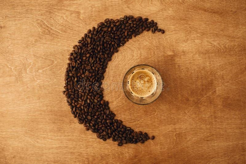 HeißEspresso mit Schaumschaum in Glasbecher und aromatisch geröstete Kaffeebohnen in Mondform auf Holztisch Flachlage, Leerstelle lizenzfreie stockfotografie