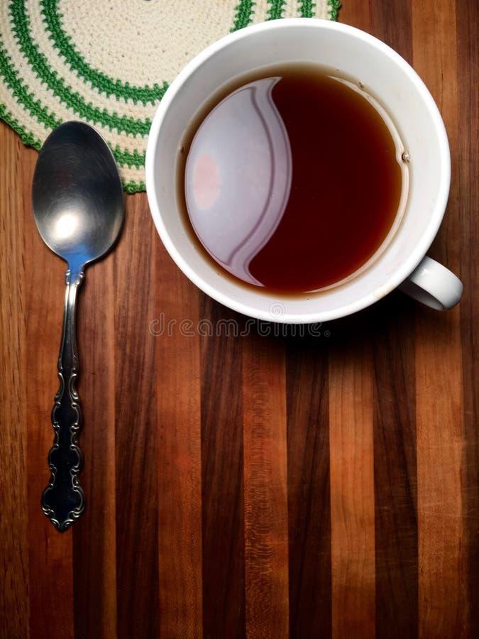 Heißgetränk auf Metzgerblocktafel mit Weinlesedoily und -löffel lizenzfreie stockbilder