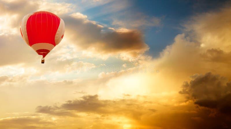 Heißluft-Ballon, der über goldenen Sonnenuntergang-Himmel fliegt stockbild