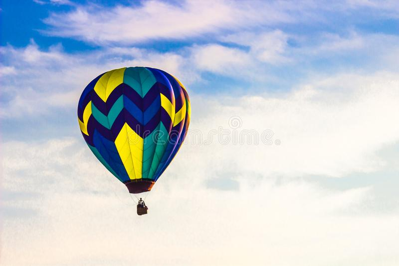 Heißluft-Ballon am frühen Morgen mit blauem Himmel u. Wolken stockbild