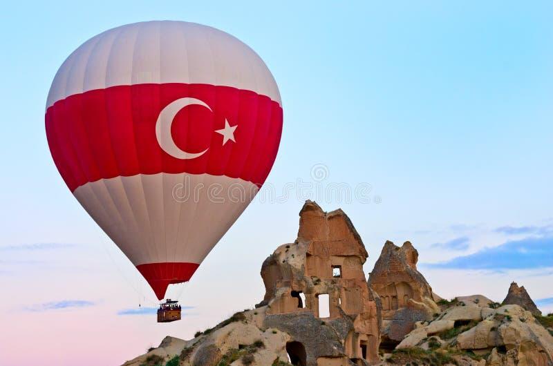 Heißluft steigt über Berglandschaft in Cappadocia, die Türkei im Ballon auf stockbilder