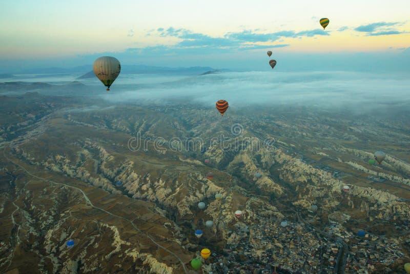 Heißluft steigt über Berglandschaft in Cappadocia, Nationalpark Goreme, die Türkei im Ballon auf Vogelperspektive vom Luftballon lizenzfreies stockbild