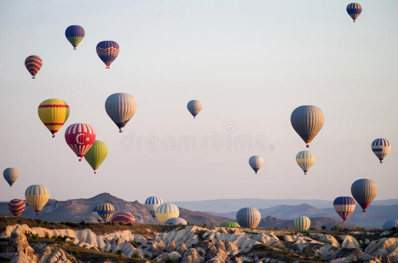 Heißluft steigt bei dem Sonnenaufgang im Ballon auf, der über Cappadocia, die Türkei fliegt Ein Ballon mit einer Flagge von der T lizenzfreie stockfotos