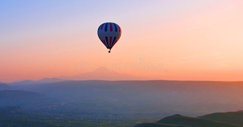 Heißluftballon, der über erstaunliche Landschaft bei Sonnenaufgang, Cappad fliegt lizenzfreie stockfotografie
