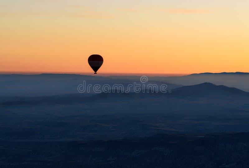 Heißluftballon, der über Tal bei Sonnenaufgang fliegt Cappadocia Die Türkei lizenzfreies stockfoto