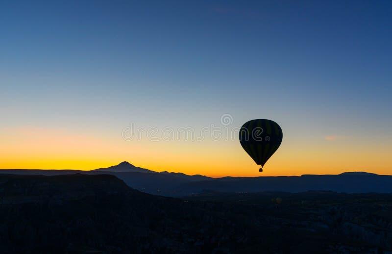 Heißluftballon, der über Tal bei Sonnenaufgang fliegt Cappadocia Die Türkei lizenzfreies stockbild