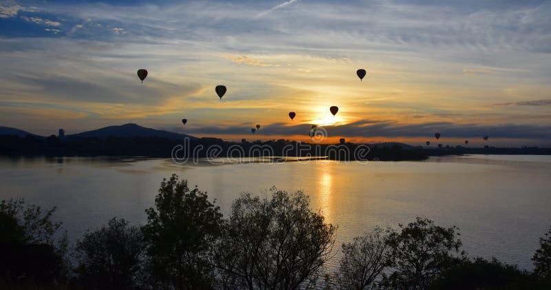 Heißluftballone, die in die Luft über See Burley Griffin fliegen lizenzfreies stockbild
