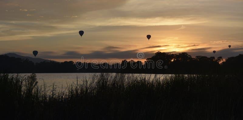 Heißluftballone, die in die Luft über See Burley Griffin fliegen lizenzfreie stockfotos