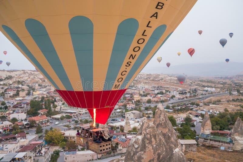 Hei?luftballonfliegen ?ber Goreme-Dorf in Cappadocia, die T?rkei lizenzfreies stockbild