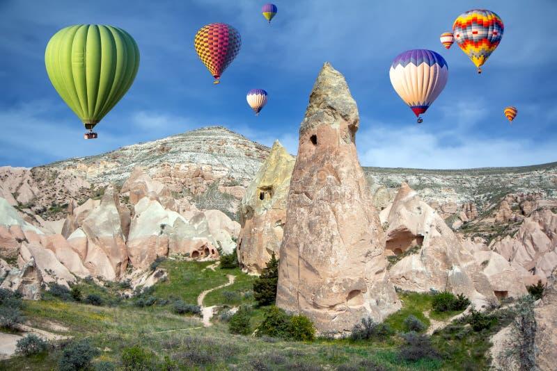 Heißluftballons am Himmel über der Höhlenstadt, Rosa Tal, Kappadokien, Türkei lizenzfreies stockfoto